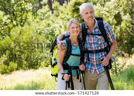 Senior couple standing with their stick in a forest