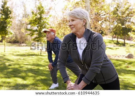 Senior Couple Stretching Whilst Exercising Together In Park #610944635