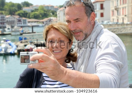 Senior couple taking picture of themselves in touristic city - stock photo