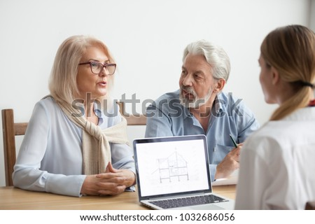 Senior couple talk to real estate agent about house purchase at meeting, interior designer advisor consulting older family with home plan on laptop screen, aged man and woman negotiating with realtor Photo stock ©