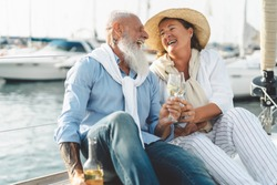 Senior couple toasting champagne on sailboat vacation - Happy elderly people having fun celebrating wedding anniversary on boat trip - Love relationship and travel lifestyle concept