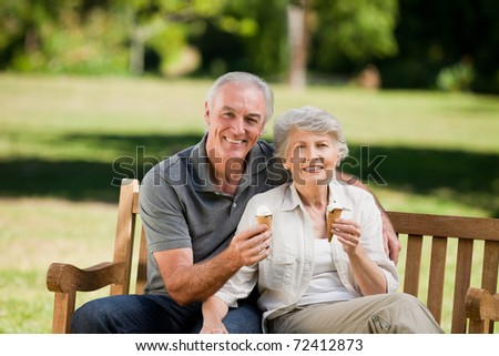 Senior couple toasting in the park on a bench