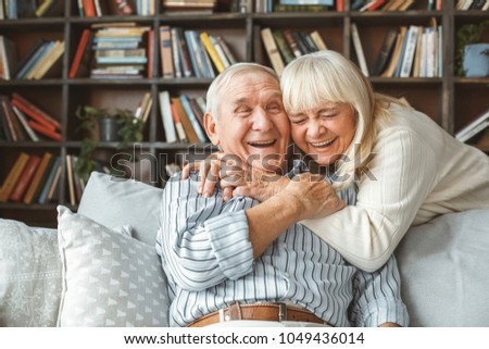 Senior couple together at home retirement concept hugging laughing