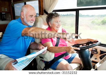 Senior couple traveling in their motor home.  The husband is giving directions to the wife.