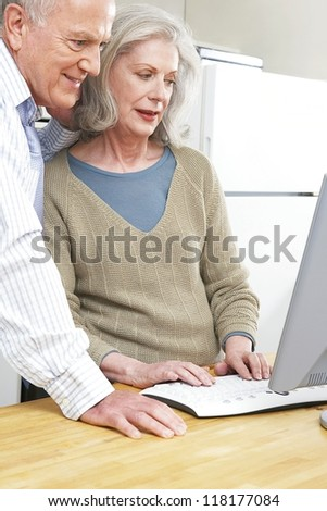 Senior couple using a computer both smiling and looking at the screen