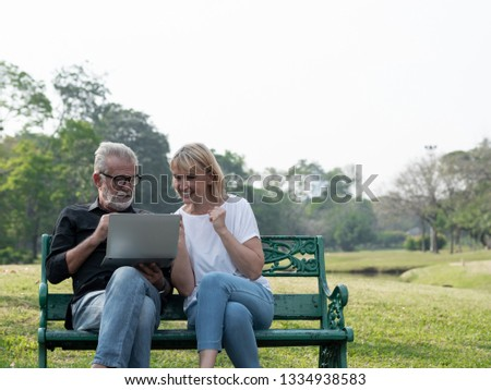 Senior couple using a laptop celebrate, success or happy pose in a park on a sunny day. relax in the forest spring summer time. free time, lifestyle retirement grandparents concept.