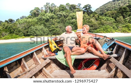 Senior couple vacationer relaxing at island hopping tour after beach exploration during snorkel boat trip in Thailand - Active elderly and travel concept around the world - Warm day bright filter