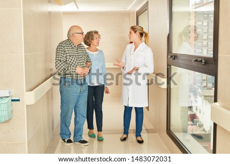 Senior couple visits nursing home and talks to doctor or geriatric nurse #1483072031