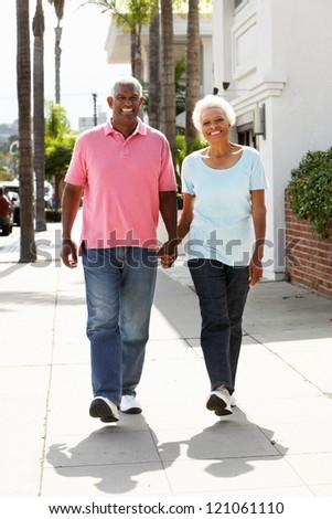 Senior Couple Walking Along Street Together
