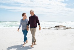 Senior couple walking and looking at each other at beach. Happy mature couple in love walking barefoot at sea shore. Loving retired man with beautiful woman relaxing at the ocean with copy space.