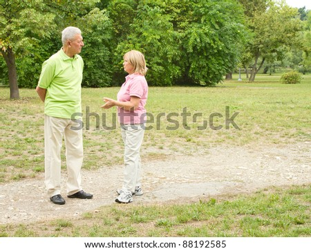 Senior couple walking and speaking in the park.