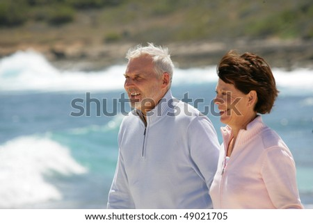 Senior couple walking by the beach