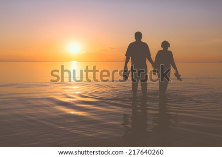 Senior couple walking holding hands in the water at sunset