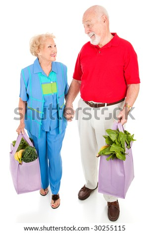 Senior couple walking home with their groceries in reusable shopping bags.  Isolated on white.