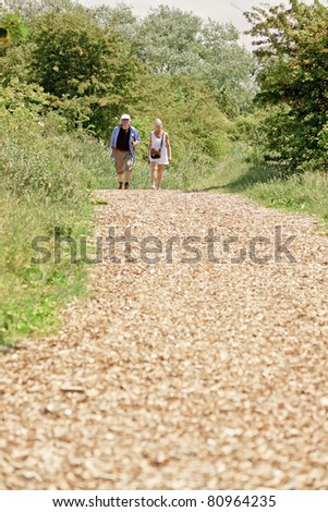 Senior couple walking in nature on summer day.