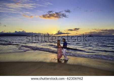 senior couple walking on a maui beach at sunset