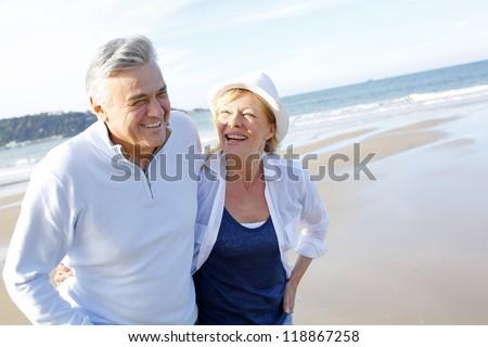 Senior couple walking on the beach in fall season - stock photo