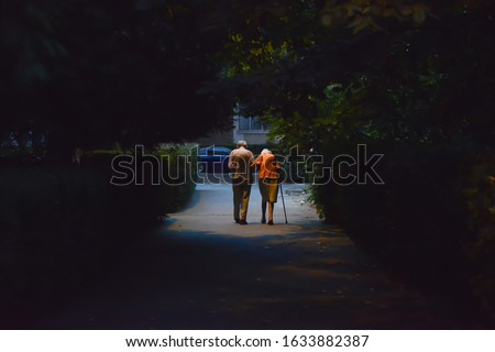 senior couple walking on the street. view from behind stock photo