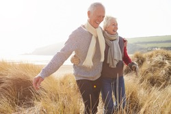 Senior Couple Walking Through Sand Dunes On Winter Beach