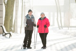 Senior couple walking with nordic walking poles in winter park. Mature woman and old man doing exercise outdoors. Healthy lifestyle concept.