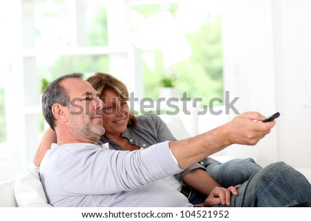 Senior couple watching television at home