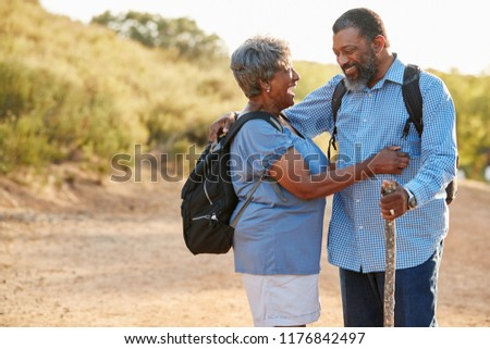 Senior Couple Wearing Backpacks Hiking In Countryside Together #1176842497