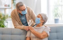 Senior couple wearing facemasks during coronavirus and flu outbreak. Virus and illness protection, home quarantine. COVID-2019. Taking on or taking off masks.