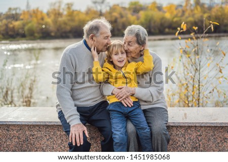 Senior couple with baby grandson in the autumn park. Great-grandmother, great-grandfather and great-grandson