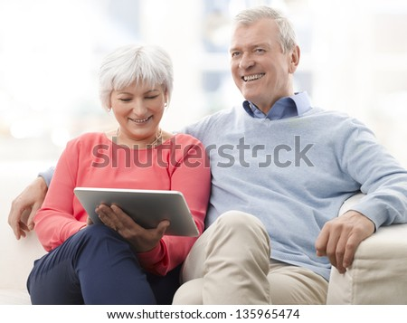 Senior couple with digital tablet surfing on the internet at home