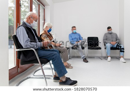 Senior couple with face masks sitting in a waiting room of a hospital together with a young and mature man - focus on the old man in the foreground Stockfoto ©