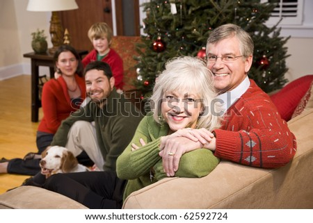 Senior couple with family by Christmas tree - three generations