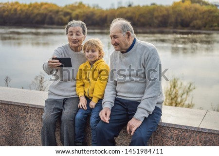 Senior couple with great-grandson take a selfie in the autumn park. Great-grandmother, great-grandfather and great-grandson