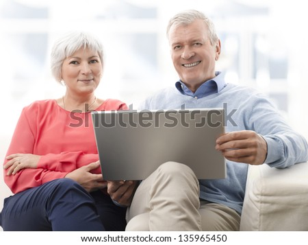 Senior couple with laptop surfing on the internet at home