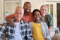 Senior couple with mature man and african woman posing for a photo sitting at courtyard. Portrait of happy multiethnic people on couch outdoor. Cheerful men and beautiful women looking at camera.