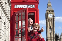 Senior couple with red telephone box in London. Big Ben in the background.