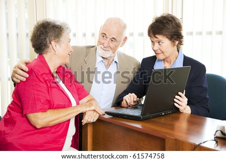 Senior couple with their financial adviser, going over their retirement income on her computer.