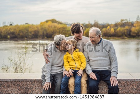 Senior couple with with grandson and great-grandson in the autumn park. Great-grandmother, great-grandfather and great-grandson