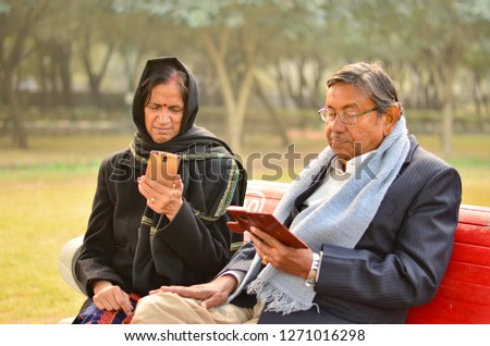 Senior couple working on mobile and talking, smiling, laughing  in a park in New Delhi, India