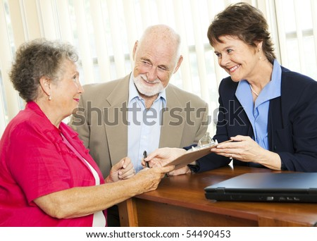 Senior couple working with a broker or adviser, signing paperwork.