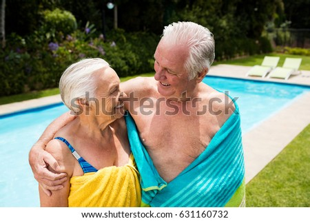 Senior couple wrapped in towel at poolside #631160732