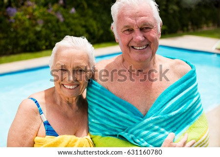 Senior couple wrapped in towel at poolside #631160780
