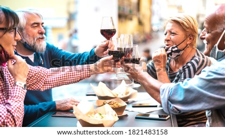 Senior couples toasting red wine at restaurant bar with face masks - New normal lifestyle concept with happy people having fun together outdoors - Bright filter with focus on central glasses ストックフォト ©