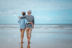 Senior couples walking on the beach at sunny day, plan life insurance with the concept of happy retirement.