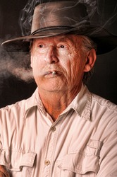 Senior cowboy hat and wearing a smoking a cigarette