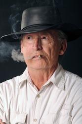 Senior Cowboy smoking a cigarette and wearing a cowboy hat