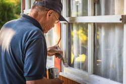 Senior craftsperson is painting house exterior. Home improvement. Old man repairing window frame.