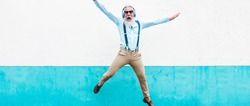 Senior crazy man jumping and listening music outdoor - Happy mature male celebrating and dancing outside - Joyful elderly lifestyle concept - Focus on his face