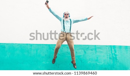 Senior crazy man jumping and listening music outdoor - Happy mature male celebrating and dancing outside - Joyful elderly lifestyle concept - Focus on him #1139869460