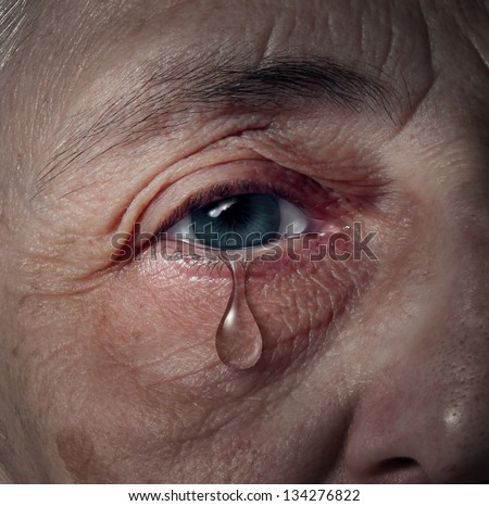 Senior depression and elderly mental health issues related to loneliness and emotional illness based on grief or chemical imbalance as anxiety in a close up of an aging human eye crying a tear drop.