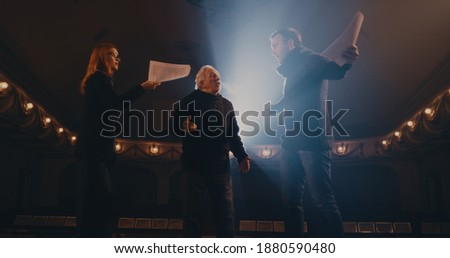 Senior director helping man and woman to act out argument scene during rehearsal on stage in theater Сток-фото ©